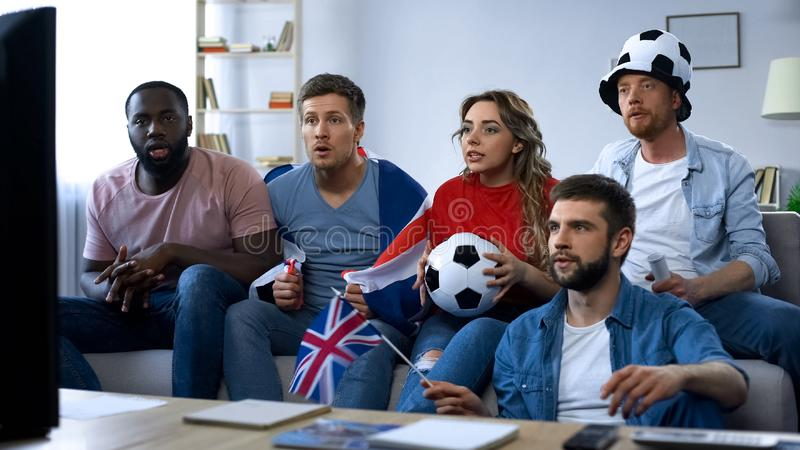 Multiethnic British friends watching football match at home, supporting team stock photography