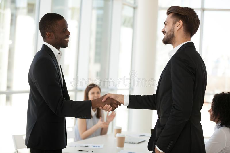 Multiethnic business partners handshake closing deal at briefing. Excited diverse partners handshake after successful business briefing in office, boss shake royalty free stock photography