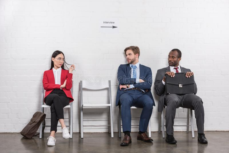 multiethnic business people looking at each other while waiting stock photography