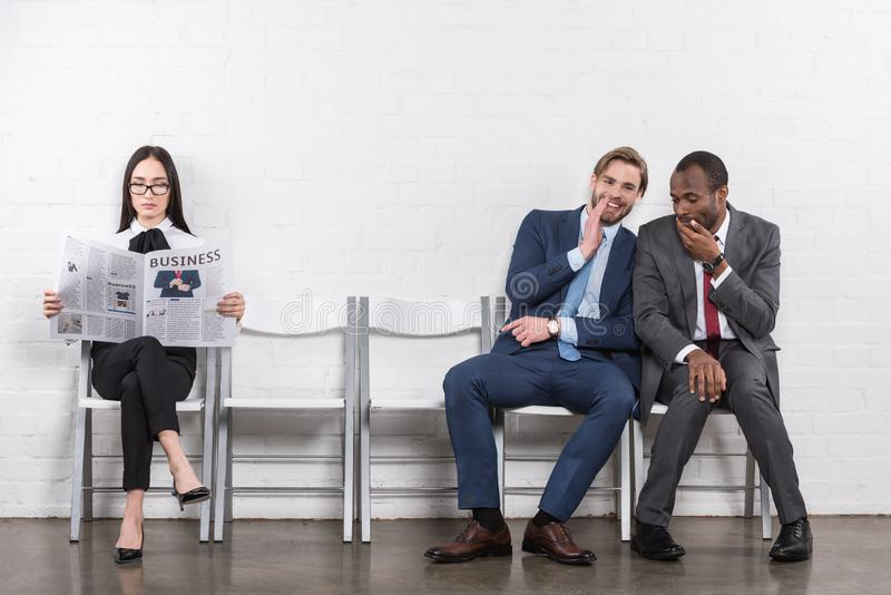 multiethnic businessmen gossiping and asian businesswoman royalty free stock photo