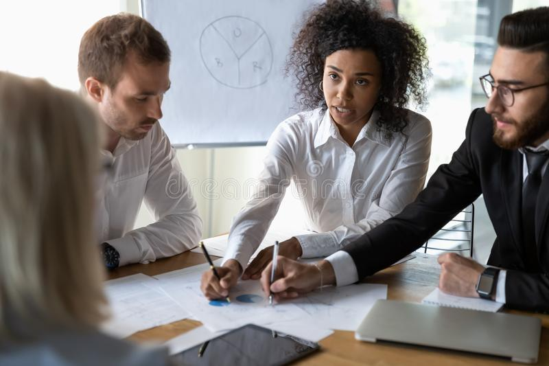 Multiethnic colleagues discussing financial paperwork at briefing royalty free stock images
