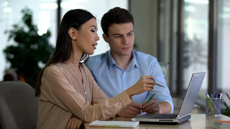 Multiethnic colleagues discussing new project looking laptop, business team royalty free stock photos