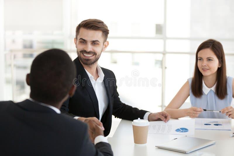 Multiethnic colleagues handshake getting acquainted at meeting. Smiling Caucasian men handshake black colleague getting acquainted at office meeting, multiethnic stock photo