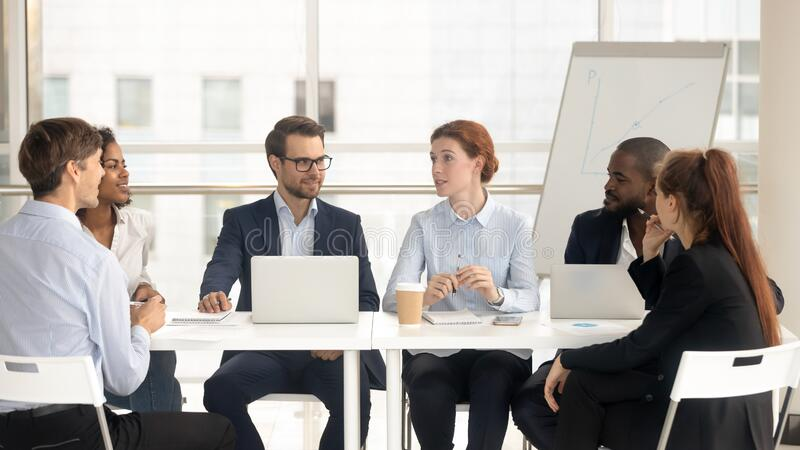 Multiethnic colleagues negotiate discussing project in boardroom royalty free stock images