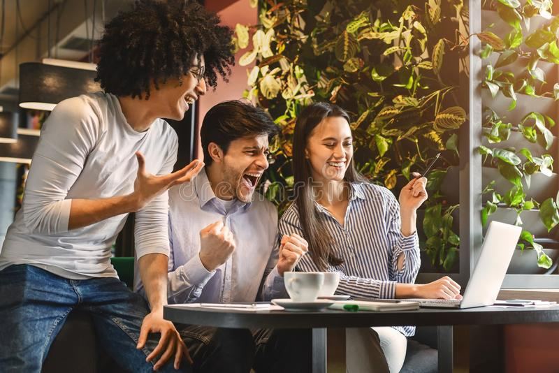 Multiethnic college group celebrate win success in cafe royalty free stock image