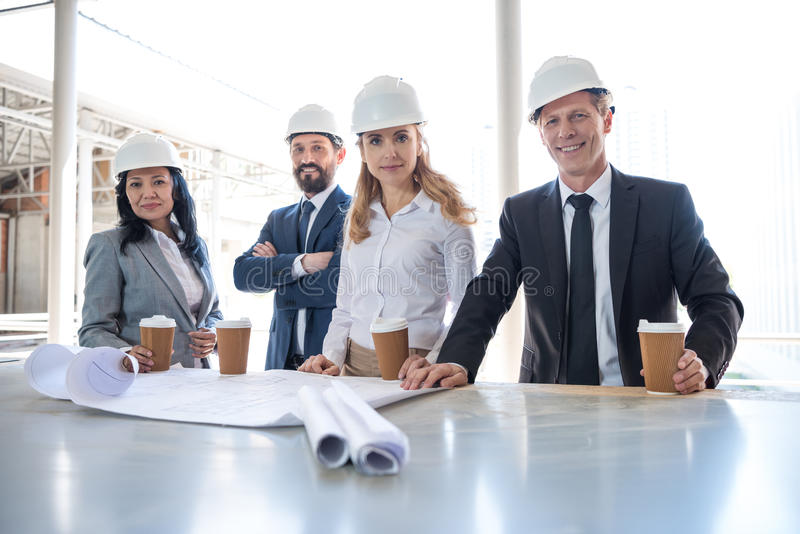 Multiethnic contractors in formal wear working with blueprints at construction area. Team of multiethnic contractors in formal wear working with blueprints at stock photos