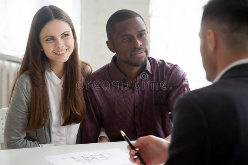 Multiethnic couple consulting real estate agent on buying house. Multiethnic millennial couple visiting real estate agent buying first home together, broker royalty free stock image