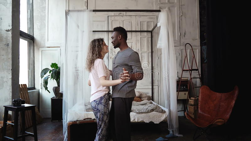 Multiethnic couple dancing in pajamas. African male and Caucasian female look happy, laughing and smiling, holding hands royalty free stock images