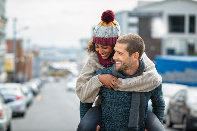 Multiethnic couple having fun in winter royalty free stock photography