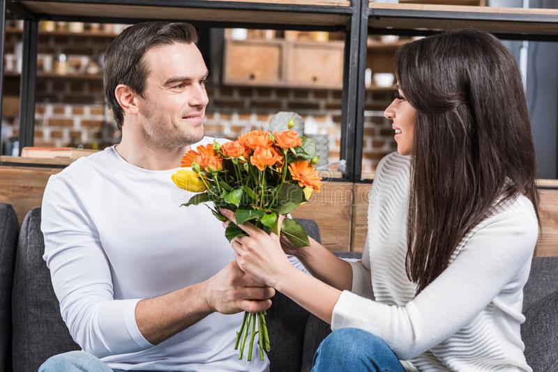 Multiethnic couple looking at each other while man. Multiethnic couple looking at each other while men presenting bouquet of flowers to woman stock photos