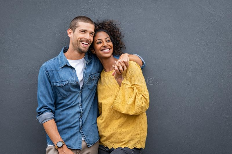 Multiethnic couple in love standing and holding hands stock images