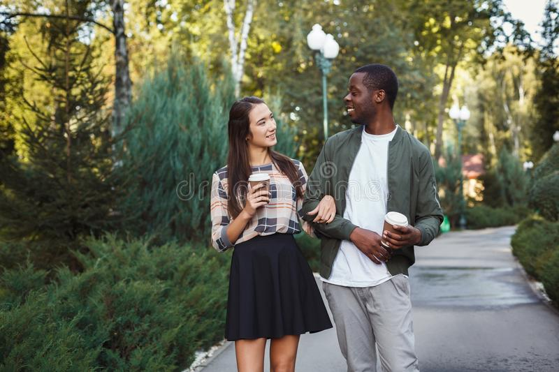 Multiethnic couple in love walk in park stock image
