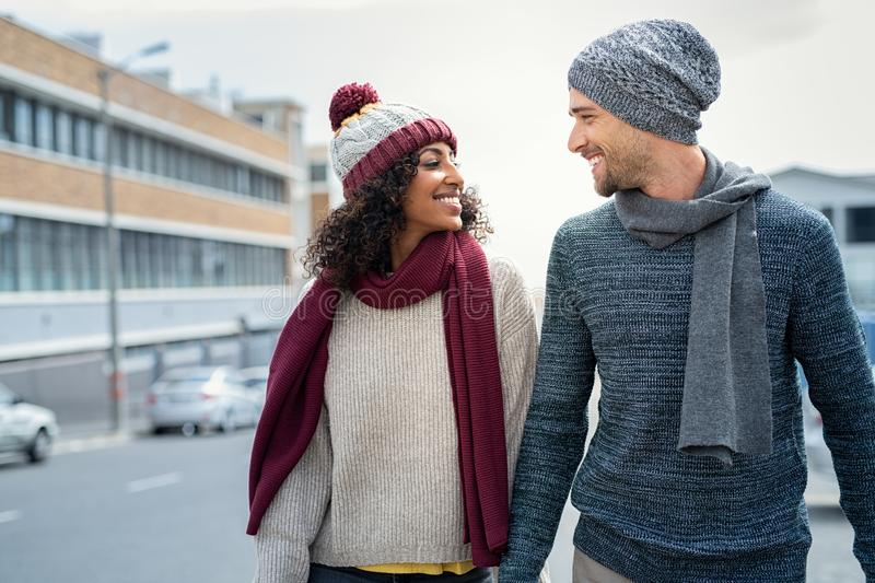 Multiethnic couple in love walking during winter royalty free stock image