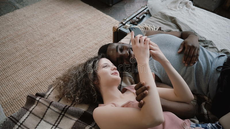 Multiethnic couple lying on bed. Man and woman laughing, using a smartphone. Male and female spend time together. stock images