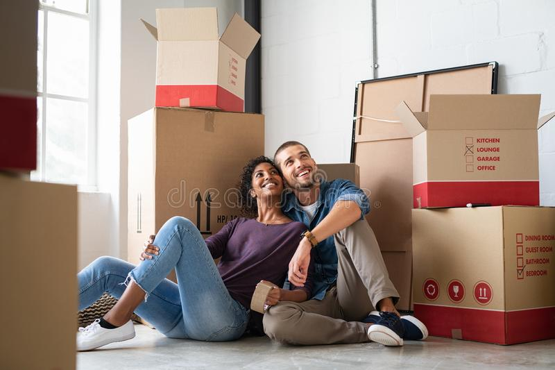 Multiethnic couple in new home with boxes royalty free stock photo