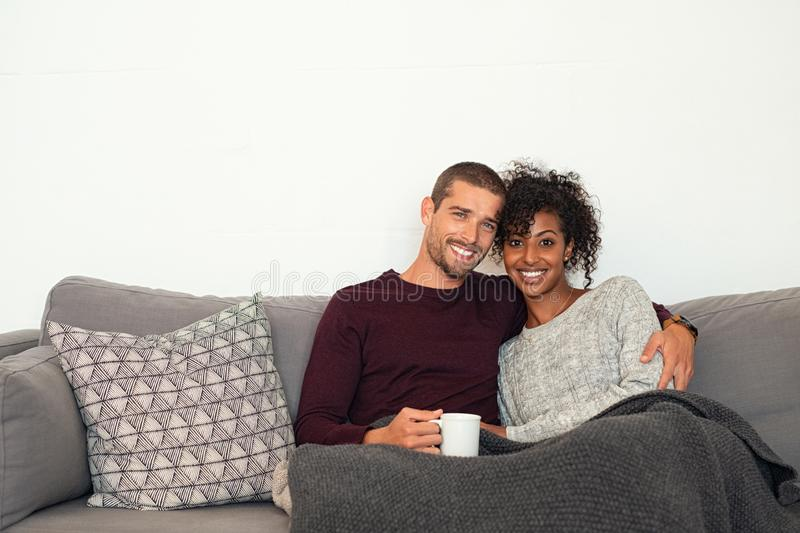 Multiethnic couple sitting on couch hugging stock image