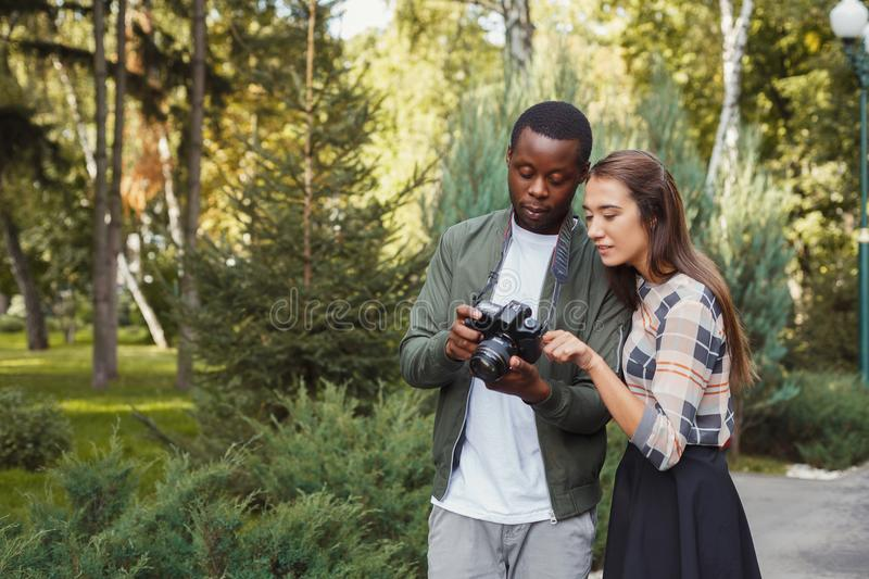 Multiethnic couple watching pictures on camera stock photos