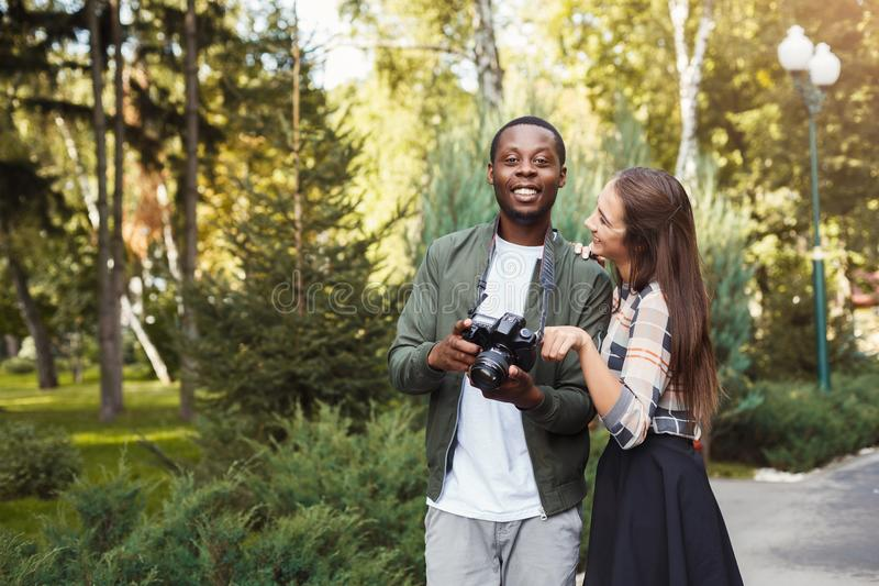 Multiethnic couple watching pictures on camera royalty free stock images