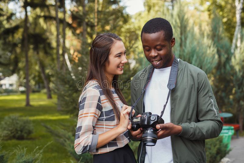 Multiethnic couple watching pictures on camera royalty free stock photos