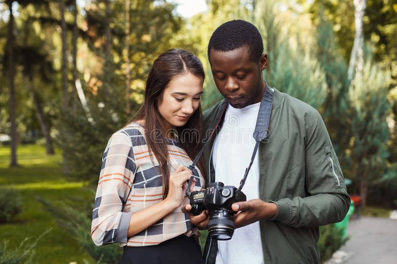 Multiethnic couple watching pictures on camera stock photo