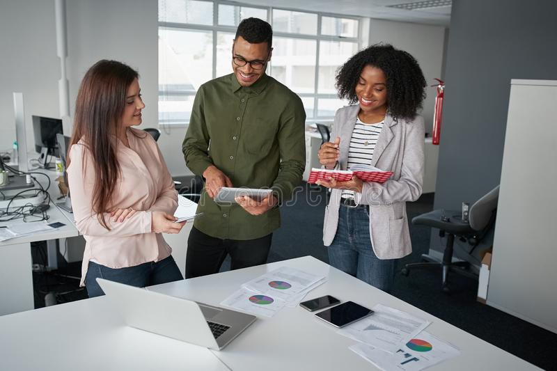 Multiethnic coworkers team working new startup project at modern office analyzing business documents, using digital royalty free stock photos