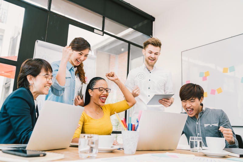 Multiethnic diverse group of coworkers celebrate together with laptop and tablet. Creative team or casual business colleague stock photo
