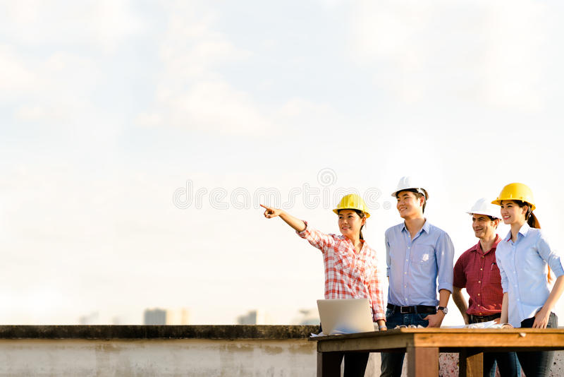 Multiethnic diverse group of engineers or business partners at construction site, pointing toward copy space on sky during sunset royalty free stock images