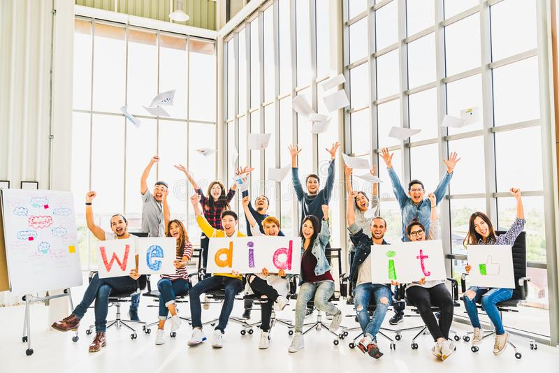 Multiethnic diverse group of happy business people cheering together, celebrate project success with papers wrote words We did it stock image