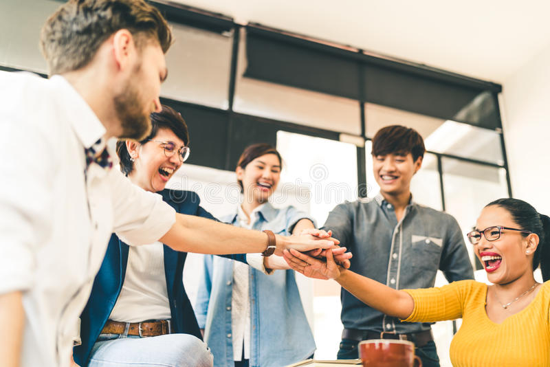 Multiethnic diverse group of happy colleagues join hands together. Creative team, casual business coworker, or college students. In project meeting at modern royalty free stock photography