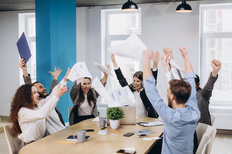 Multiethnic diverse happy team celebrate project success throw paper up together. Corporate community, college graduation, startup royalty free stock image
