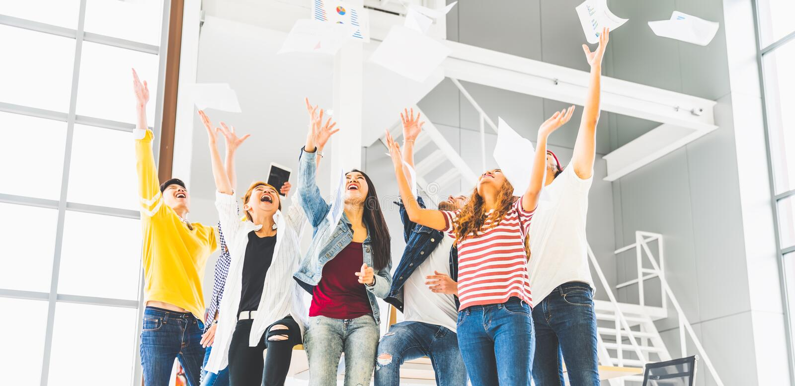 Multiethnic diverse happy team celebrate project success throw paper up together. Corporate community, or small business concept. Multiethnic diverse happy team royalty free stock image
