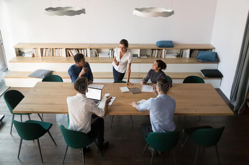 Multiethnic employees discuss ideas with female team leader. Top view of multiethnic work group sit at office desk discuss business project with female team royalty free stock photography