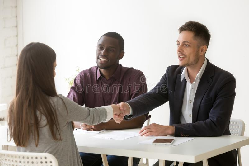 Multiethnic employers greeting female job candidate with handsha. Multiethnic hr team welcoming female job candidate with handshake, male Caucasian employer stock photography