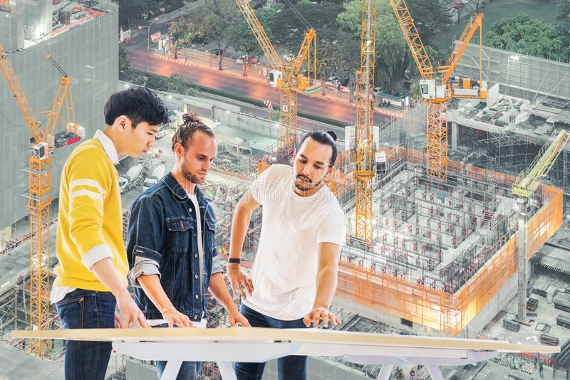 Multiethnic engineer, architect team work together on building development project planning, under construction site background stock photo