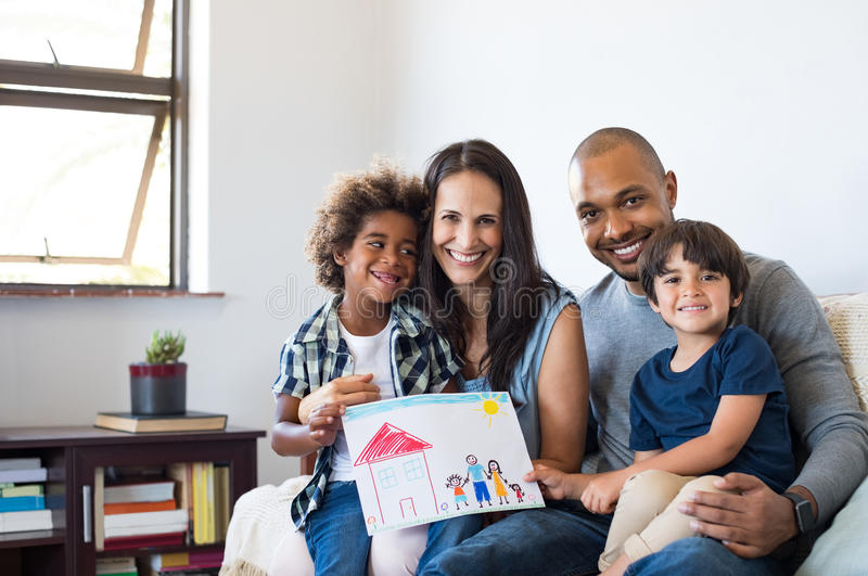 Multiethnic family on sofa. Proud parents showing family painting of son sitting on sofa at home. Smiling mother and father with children's drawing of a royalty free stock images