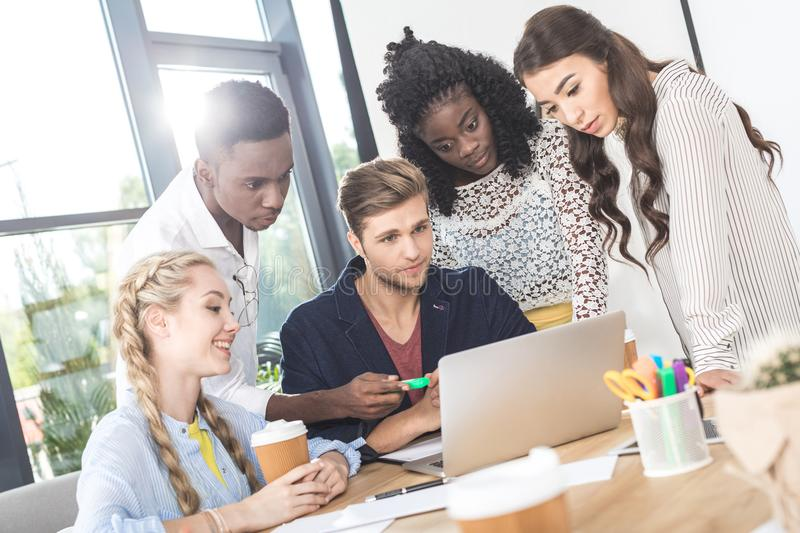 multiethnic focused business team working on laptop together at workplace royalty free stock photos