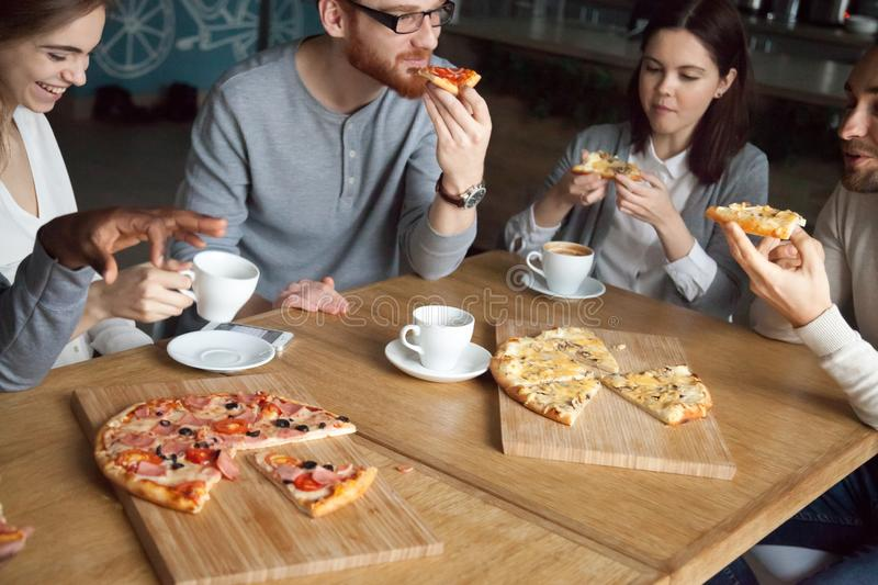 Multiethnic friends talk and laugh enjoying pizza in pizzeria royalty free stock photography