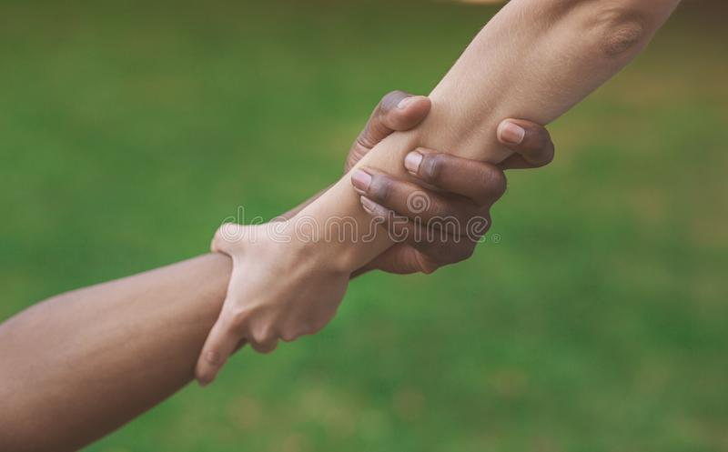 Multiethnic friends helping hand outdoor, copy space stock image
