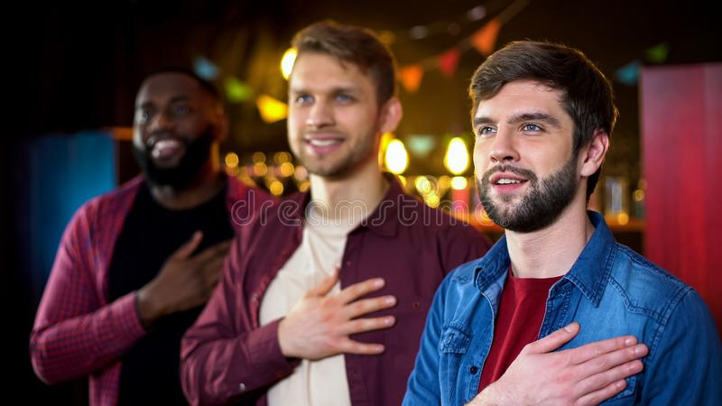 Multiethnic friends listening to anthem before soccer match, results time in pub. Stock photo stock photography