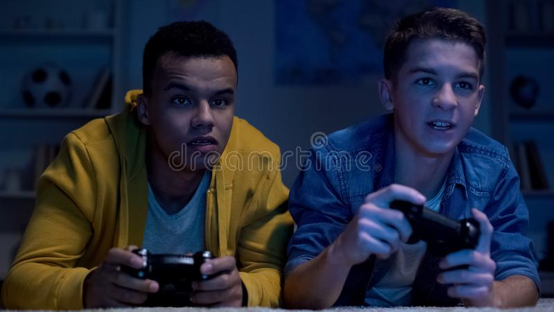 Multiethnic friends playing video games late at night, lazy college students royalty free stock image