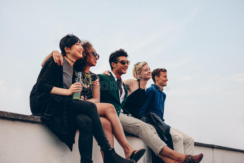 Multiethnic friends relaxing on terrace. Shot of young men and women relaxing together on rooftop. Multiethnic friends relaxing on terrace royalty free stock photo