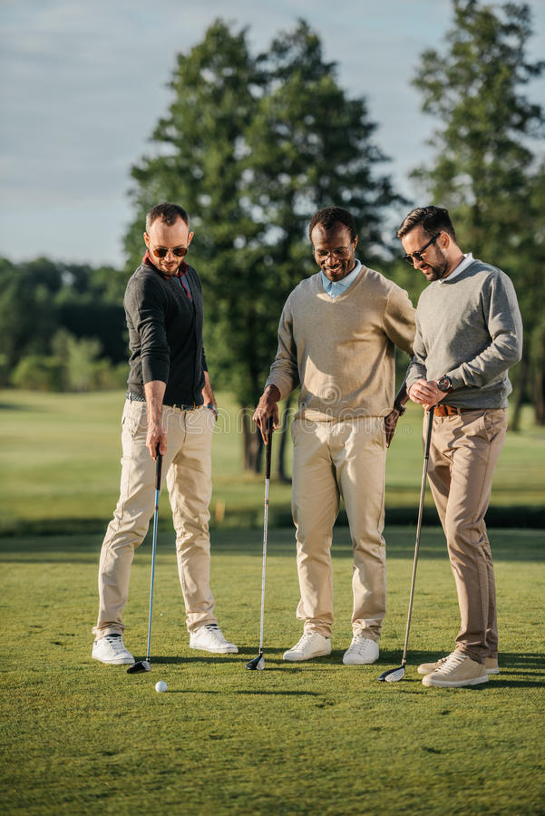 Multiethnic friends spending time together while playing golf on golf course royalty free stock photo