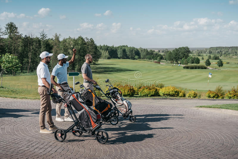 Multiethnic friends with sport equipment going to the golf course. Young multiethnic friends with sport equipment going to the golf course stock image