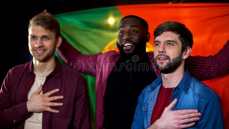 Multiethnic friends supporting portuguese team, singing anthem and holding flag. Stock photo royalty free stock image