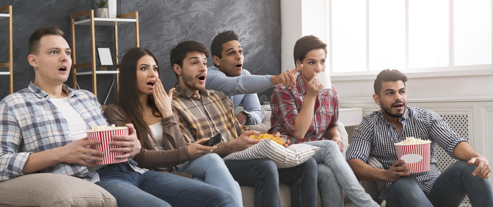 Multiethnic friends watching horror movie with popcorn at home. Shocked multiethnic friends watching horror movie with popcorn at home, panorama with copy space royalty free stock photos