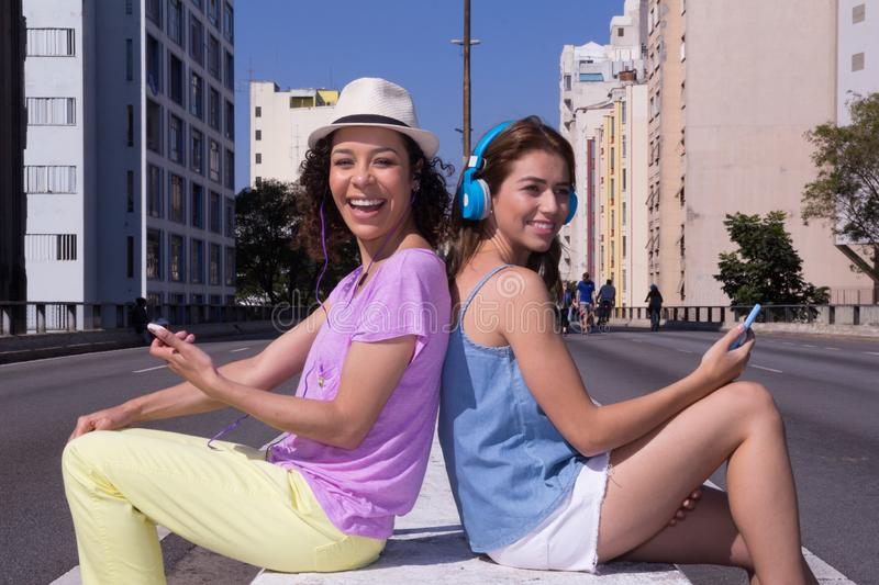 Multiethnic girls back to back laughing and looking at camera in royalty free stock photo