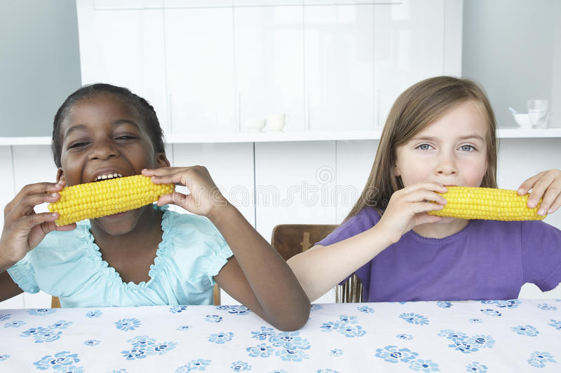 Multiethnic Girls Eating Corn Cobs royalty free stock photos