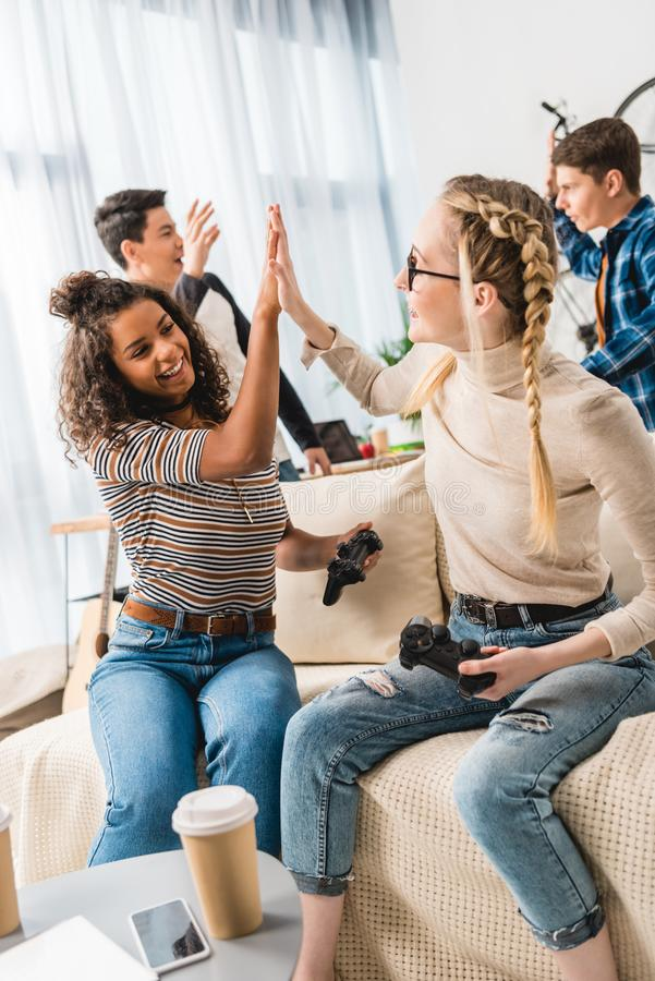 multiethnic girls giving high five for winning boys in video game stock image