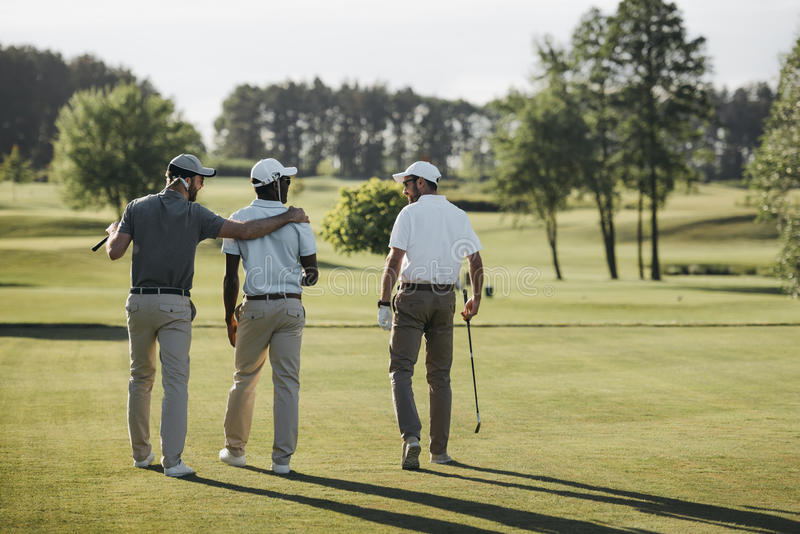 Multiethnic golf players hugging and walking on golf course. Back view of multiethnic golf players hugging and walking on golf course stock photos