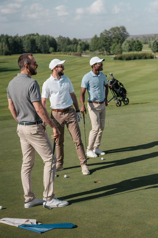Multiethnic golf players looking away while standing on pitch stock images